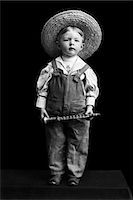 1800s 1890s TURN OF THE CENTURY BOY IN OVERALLS & STRAW HAT HOLDING SMALL CLARINET-LIKE INSTRUMENT Stock Photo - Premium Rights-Managednull, Code: 846-06112251