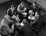 1950s GROUP OF SIX MEN TALKING AROUND A  CONFERENCE TABLE