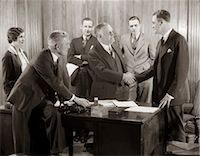 1930s GROUP BUSINESS MEN AND WOMAN IN OFFICE BOSS SHAKING HANDS WITH NEW HIRE Stock Photo - Premium Rights-Managednull, Code: 846-06112262