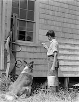 farm and boys - 1930s BOY PAINTING SIDE OF FARM HOUSE WITH COLLIE SITTING BESIDE HIM WATCHING Stock Photo - Premium Rights-Managednull, Code: 846-06112278