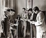 1930s BROKERS BUSINESSMEN READING TICKER TAPE AS IT COMES OUT OF GLASS DOMED MACHINE