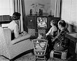 1950s BACK VIEW OF FAMILY OF 4 GATHERED AROUND TV SET WATCHING CLOWN WITH BALLOONS