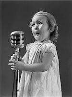 1940s LITTLE GIRL MAKING FACE SINGING INTO MICROPHONE Stock Photo - Premium Rights-Managednull, Code: 846-06112340