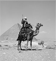 1950s NATIVE MAN ARAB RIDING CAMEL NEAR THE GREAT PYRAMID AT GIZA AND THE SPHINX Stock Photo - Premium Rights-Managednull, Code: 846-06112344