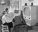 1950s BOY AND GIRL WATCHING TV IN LIVING ROOM