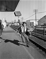 1950s BUSINESSMAN WITH BRIEFCASE IN AIR RUNNING AFTER DEPARTING TRAIN Stock Photo - Premium Rights-Managednull, Code: 846-06112366