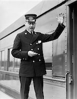 1930s CONDUCTOR MAKING FINAL BOARDING CALL OUTSIDE TRAIN Stock Photo - Premium Rights-Managednull, Code: 846-06112368