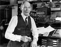1930s 1940s OLDER MAN WEARING SHIRTSLEEVES VEST LEANING ON TYPE DRAWER CABINET IN OLD PRINTING SHOP SMOKING CIGAR AND TALKING Stock Photo - Premium Rights-Managednull, Code: 846-06112374