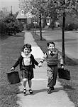 1950s BOY AND GIRL CARRYING BOOK BAGS WALKING TOGETHER HAND IN HAND ON SIDEWALK TO OR FROM SCHOOL OUTDOOR