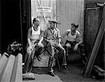 1930s 1940s THREE WORKMEN SITTING UNDER NO SMOKING SIGN SMOKING CIGARETTE AND PIPE JOB SAFETY