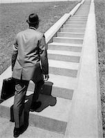 1960s BUSINESS MAN IN SUIT & FEDORA HOLDING BRIEFCASE STARTING UP LONG FLIGHT OF CEMENT STAIRS AHEAD OF HIM Stock Photo - Premium Rights-Managednull, Code: 846-06112444