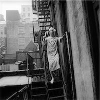 1970s MAN IN NIGHTGOWN AND CAP CARRYING CANDLE SLEEPWALKING DOWN FIRE ESCAPE OUTDOOR Stock Photo - Premium Rights-Managednull, Code: 846-06112465