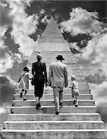 1950s BACK VIEW MONTAGE FAMILY FATHER MOTHER DAUGHTER SON WALKING UP STAIRWAY TOGETHER INTO THE SKY SYMBOLIC Stock Photo - Premium Rights-Managednull, Code: 846-06112471
