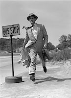 1950s SALESMAN RUNNING TO CATCH BUS AT BUS STOP SIGN OUTDOOR Stock Photo - Premium Rights-Managednull, Code: 846-06112489