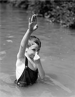 1930s BOY WEARING OVERALLS AS BATHING SUIT STANDING IN CREEK ARM UP & HOLDING NOSE TO GO UNDERWATER Stock Photo - Premium Rights-Managednull, Code: 846-06112491