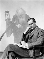 1930s MAN IN SUIT SEATED WITH BOOK IN LAP & PIPE IN HAND WITH PENSIVE LOOK WITH GRIM REAPER GHOSTED IN BACKGROUND Stock Photo - Premium Rights-Managednull, Code: 846-06112493