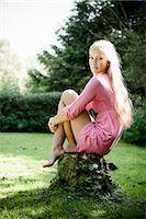 Woman sitting on stump outdoors Stock Photo - Premium Royalty-Freenull, Code: 649-06112535