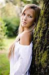 Woman leaning against tree outdoors