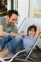 Father and son playing in deck chairs Stock Photo - Premium Royalty-Freenull, Code: 649-06112608