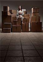 Teenage girl in pile of cardboard boxes Stock Photo - Premium Royalty-Freenull, Code: 649-06112641