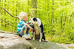 Boy sitting with dog in forest