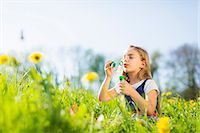 Girl blowing bubbles in field Stock Photo - Premium Royalty-Freenull, Code: 649-06112836