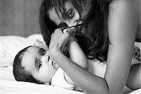 Mother and baby laying on bed Stock Photo - Premium Royalty-Freenull, Code: 649-06112943