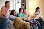Friends watching a movie in living room Stock Photo - Premium Royalty-Free, Artist: Blend Images, Code: 649-06112947