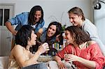 Friends laughing together in living room Stock Photo - Premium Royalty-Free, Artist: Blend Images, Code: 649-06112960