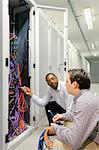 Businessmen examining wires in server Stock Photo - Premium Royalty-Free, Artist: Blend Images, Code: 649-06113264