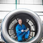 Worker sitting in airplane engine Stock Photo - Premium Royalty-Free, Artist: Blend Images, Code: 649-06113327