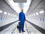 Worker standing in empty airplane Stock Photo - Premium Royalty-Free, Artist: Blend Images, Code: 649-06113337