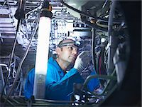 Worker adjusting airplane machinery Stock Photo - Premium Royalty-Freenull, Code: 649-06113343