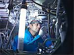 Worker adjusting airplane machinery Stock Photo - Premium Royalty-Free, Artist: Blend Images, Code: 649-06113343