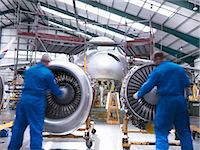 Worker pushing airplane engines on carts Stock Photo - Premium Royalty-Freenull, Code: 649-06113347