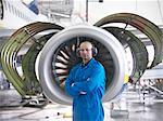 Worker standing by airplane engine Stock Photo - Premium Royalty-Free, Artist: Blend Images, Code: 649-06113362
