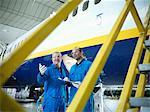 Workers talking in airplane hangar Stock Photo - Premium Royalty-Free, Artist: Blend Images, Code: 649-06113373