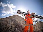 Worker standing by pile of stones Stock Photo - Premium Royalty-Free, Artist: Ed Gifford, Code: 649-06113380