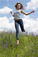 Woman leaping in tall grass Stock Photo - Premium Royalty-Freenull, Code: 649-06113576