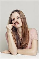 funny pose - Woman playing with hair as mustache Stock Photo - Premium Royalty-Freenull, Code: 649-06113583