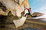 Woman climbing boulder in rocky terrain Stock Photo - Premium Royalty-Free, Artist: ableimages, Code: 649-06113931