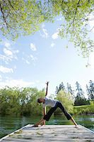 Woman practicing yoga on dock Stock Photo - Premium Royalty-Freenull, Code: 6106-06114118