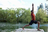 Man stretching on dock Stock Photo - Premium Royalty-Freenull, Code: 6106-06114119