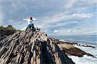 Woman outstretches arms by oceanside. Stock Photo - Premium Royalty-Freenull, Code: 6106-06114382