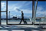 Businessman walking with suitcase outside airport Stock Photo - Premium Royalty-Free, Artist: Blend Images, Code: 614-06115988