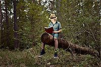 sitting under tree - Boy sitting on tree trunk reading book Stock Photo - Premium Royalty-Freenull, Code: 614-06116043