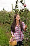 Young woman in orchard, throwing apple in the air Stock Photo - Premium Royalty-Free, Artist: Cultura RM, Code: 614-06116447