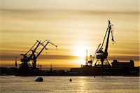 Silhouette of a commercial dock at sunset Stock Photo - Premium Royalty-Freenull, Code: 698-06116634