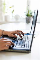 Cropped image of woman's hand typing on laptop Stock Photo - Premium Royalty-Freenull, Code: 698-06116745