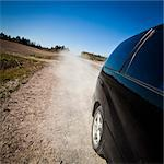 Black car moving fast on dirt road while blowing dust in air Stock Photo - Premium Royalty-Free, Artist: Blend Images, Code: 698-06117029
